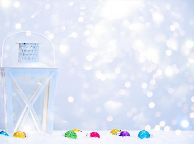 Fondo de invierno con lámpara de linterna, bolas de navidad y espacio de copia.