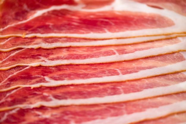 Fondo italiano cortado del jamón. vista superior, copia espacio. cierre de la textura del jamón para arriba.