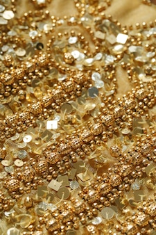 Fondo de lentejuelas y cuentas de oro. tejido brillante. la textura de la tela con lentejuelas y cornetas.
