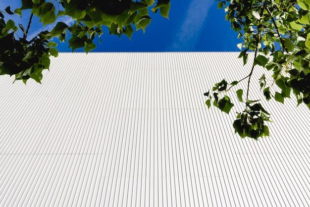 Fondo de líneas verticales metálicas y hojas verdes.