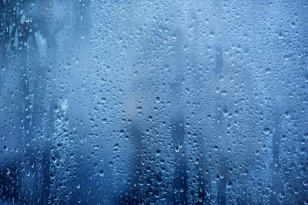 Fondo lluvioso, gotas de agua de lluvia en la ventana o en la ducha, telón de fondo de la temporada de otoño