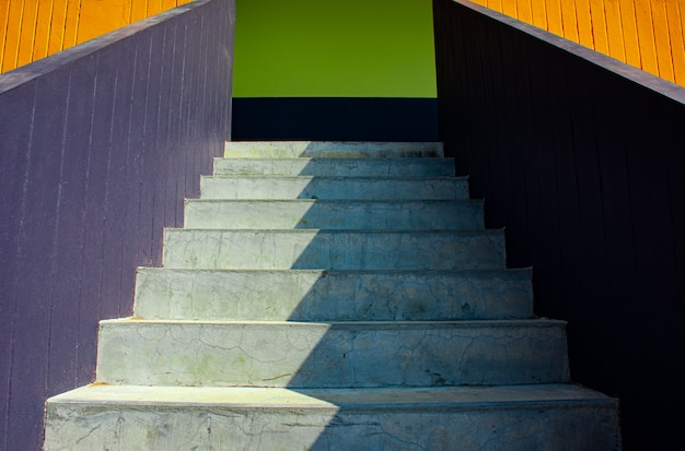 El fondo de la luz del sol y la sombra en la piedra blanca camina la superficie de la escalera colorida en ángulo bajo y la opinión de perspectiva, imagen para el concepto de diseño exterior casero de la decoración.