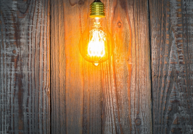 Fondo de madera con bombilla iluminada