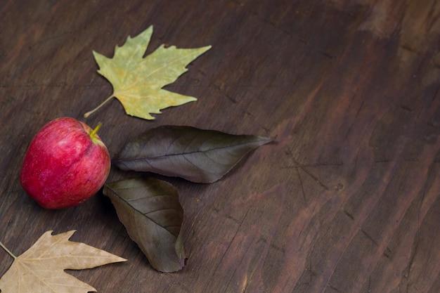 Fondo de madera de otoño con manzana y hojas secas de color amarillo.