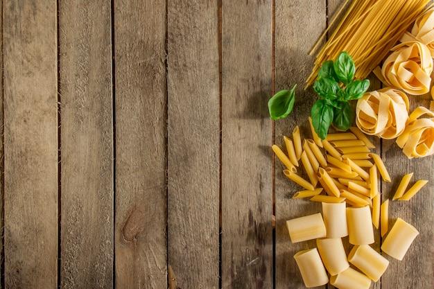 Fondo de madera con pasta italiana y albahaca