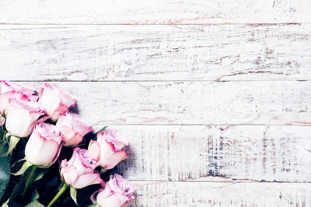 Fondo de madera con ramo de rosas rosadas.