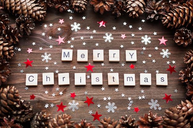 Fondo de madera rústica con piñas. fondo feliz navidad con confeti de copo de nieve brillante.
