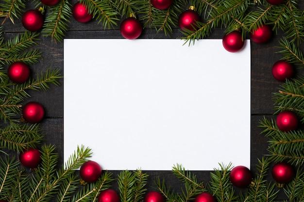 Fondo de madera con tarjeta blanca y decoración navideña.