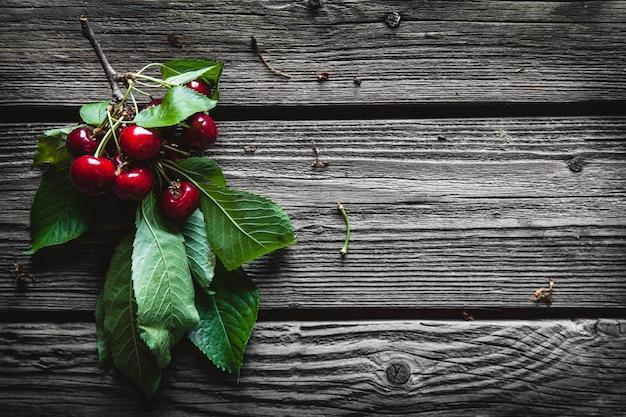 Fondo de madera con varias cerezas deliciosas en hojas verdes