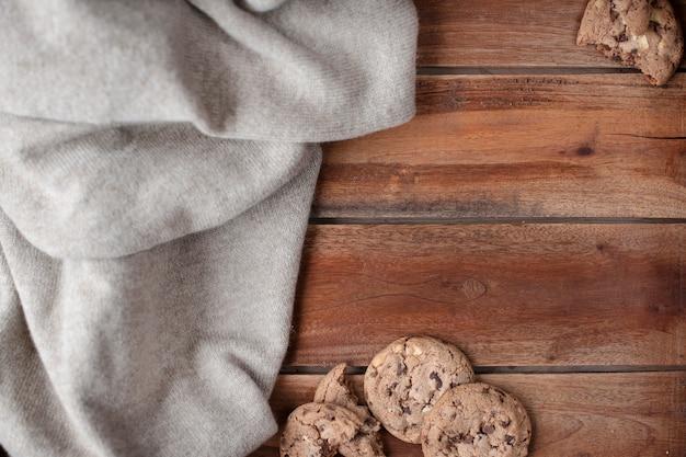 Fondo de madera vieja y suéter caliente de punto. decoración de otoño e hígado de galleta con chocolate. espacio libre para texto. vista superior copia espacio