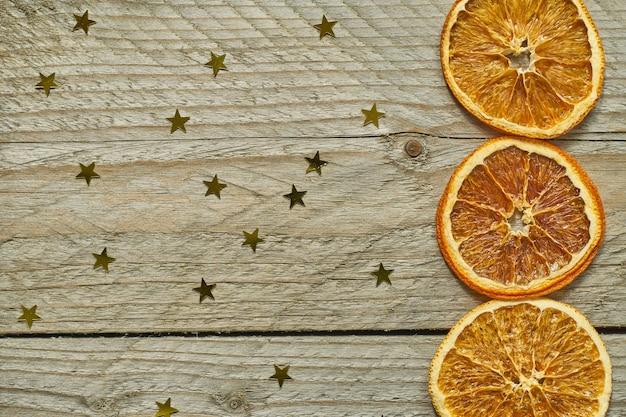 Fondo de madera vintage con corona de navidad - rodajas de naranja seca y confeti de oro en forma de estrella. vista superior con espacio de copia