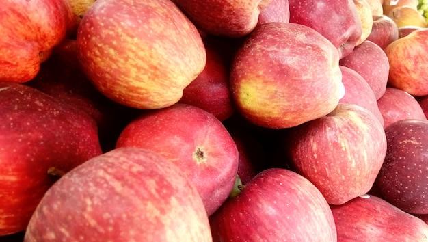 Fondo de manzanas crujientes de miel roja fresca escogida en la temporada de cosecha colocada en un mercado o bazar para la venta