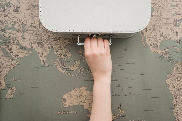Fondo de mapa del mundo con mano agarrando una maleta
