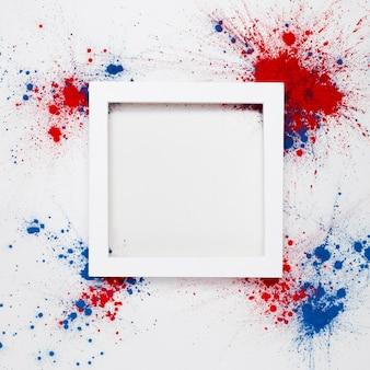 Fondo con un marco blanco con copyspace y fuegos artificiales hechos con salpicaduras de color holi