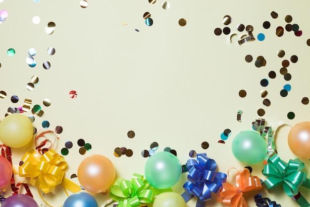 Fondo de marco de felices fiestas con globos de colores, regalos, confeti, gorro de carnaval y serpentina.