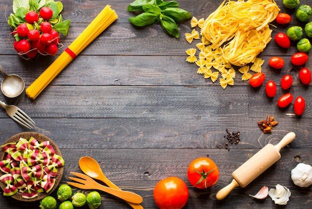 Fondo de marco de pasta, varios tipos de pasta seca con verduras y hierbas, vista superior