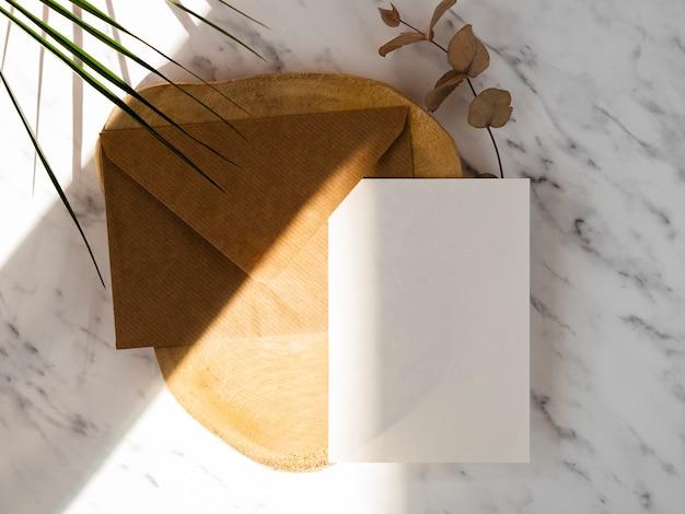 Fondo de mármol con una placa de madera con un sobre marrón y un blanco en blanco