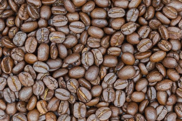 Fondo marrón asado primer de los granos de café.