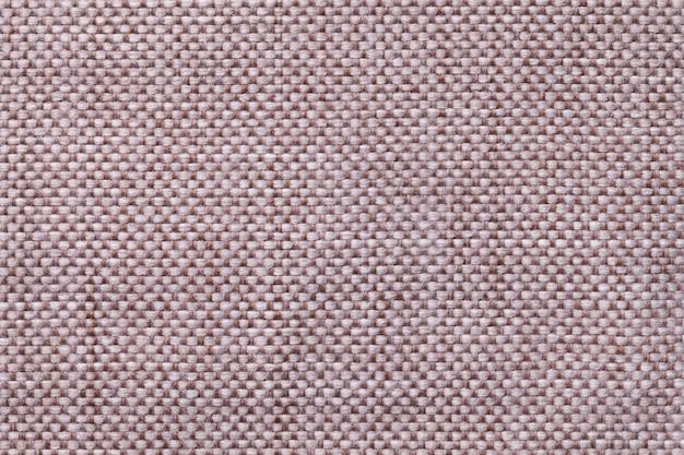 Fondo marrón claro de la materia textil con el modelo a cuadros, primer. estructura de la macro de la tela.