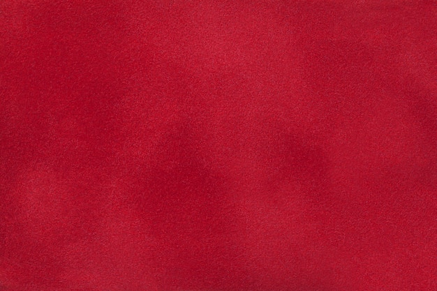 Fondo mate rojo oscuro de la tela de gamuza, primer plano.