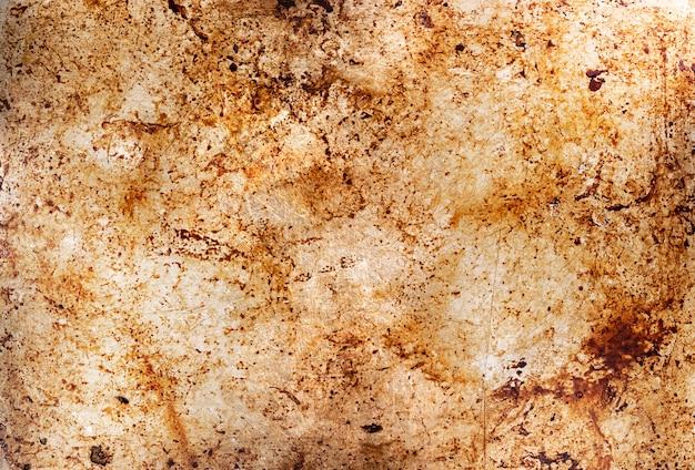 Fondo de metal con manchas de aceite, bandeja de horno sucia, superficie de la bandeja engrasada con restos de aceite después de asar alimentos