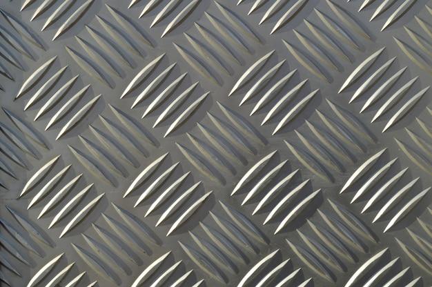 Fondo de metal con patrones repetitivos de diamantes.