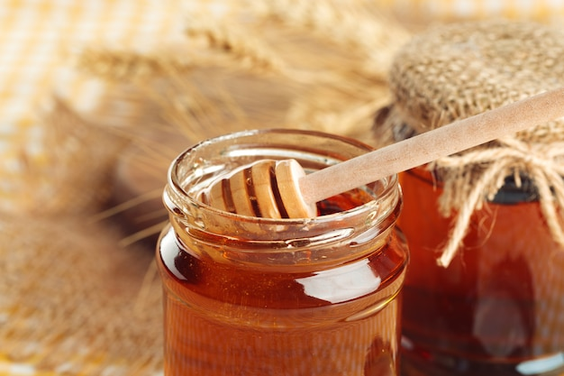 Fondo de miel dulce miel en tarro de cristal sobre fondo de madera.