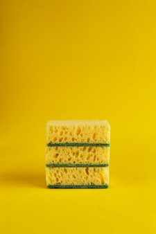 Fondo mínimo con esponjas amarillas para lavar platos. fondo amarillo de moda