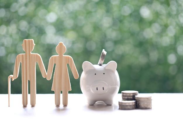 Fondo mutuo, amor pareja senior y hucha con pila de monedas dinero sobre fondo verde natural