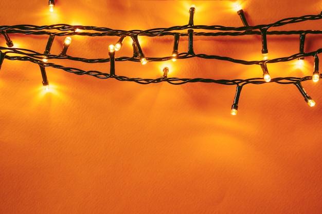 Fondo naranja con luces iluminadas de guirnalda