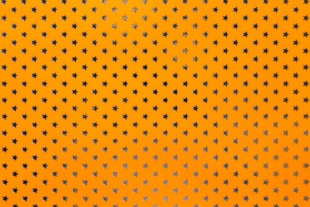 Fondo naranja de papel de aluminio con un patrón de estrellas doradas