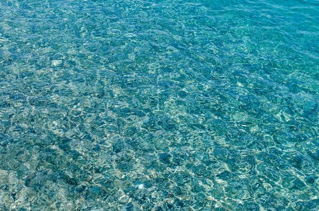 Fondo natural de agua clara de mar azul transparente. fondo azul del mar mediterráneo con pequeñas piedras. de cerca