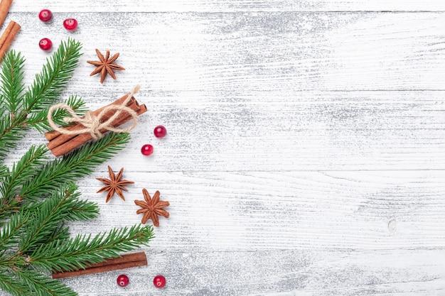 Fondo de navidad con abeto, especias y arándano rojo sobre mesa de madera