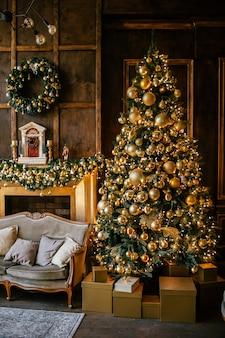 Fondo de navidad con abeto iluminado con decpration dorado y chimenea en la sala de estar. acogedora casa de vacaciones
