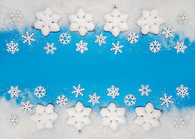 Fondo de navidad, adornos blancos, bolas de navidad y copos de nieve sobre nieve blanda, espacio de copia