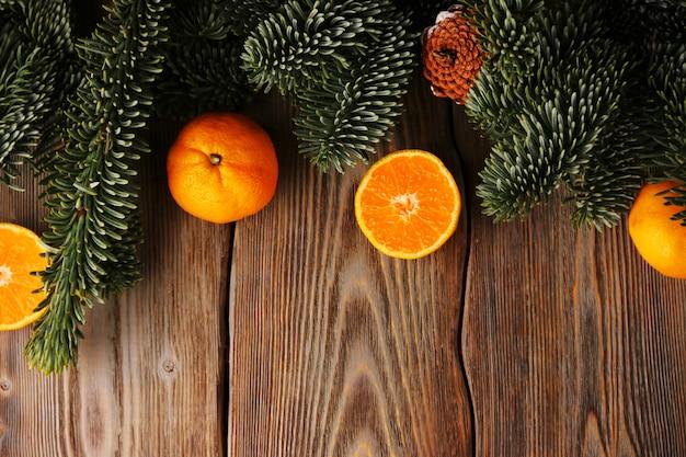 Fondo de navidad. árbol de navidad y mandarina o mandarina en mesa de madera.