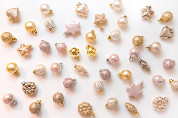 Fondo de navidad con bolas de brillo dorado y rosa sobre blanco
