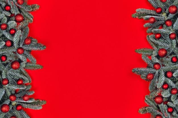 Fondo de navidad con bolas rojas en ramas de abeto.