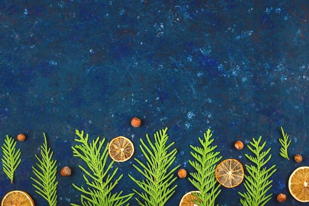 Fondo de navidad brillante azul con ramas de árbol de navidad verde y decoraciones ecológicas.