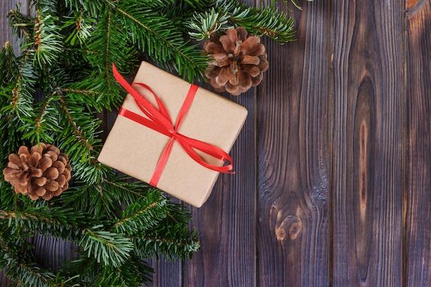Fondo de navidad con cajas de regalo decoradas y ramas de árboles de navidad.