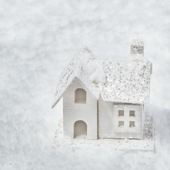 Fondo de navidad con casita blanca sobre fondo de nieve. concepto de vacaciones de invierno composición mínima.
