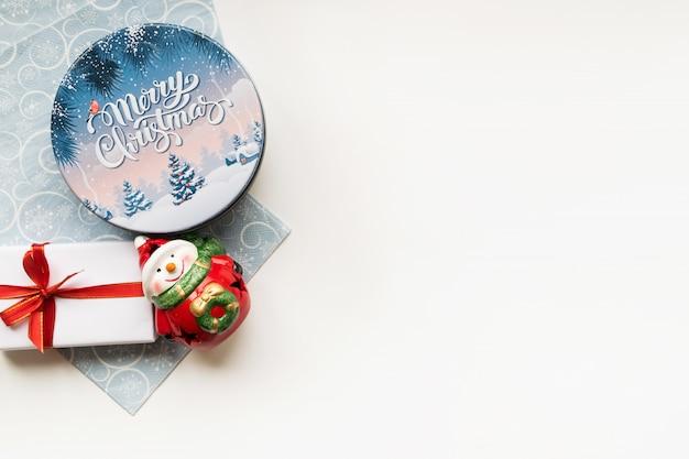 Fondo de navidad con composición decorativa de caja de navidad, muñeco de nieve de cerámica, caja de regalo y servilleta azul claro. feliz año nuevo. copyspace