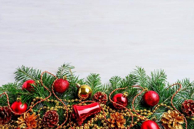 Fondo de navidad con cono de pino, decoración dorada y roja.