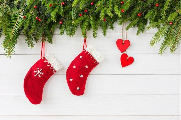 Fondo de navidad corazón rojo y calcetines rojos de navidad sobre fondo blanco de madera, abeto de navidad.