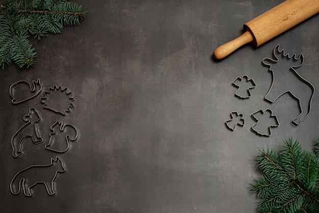 Fondo de navidad con cortadores de galletas, rodillo y ramas de pino con espacio de copia, suministros para hornear galletas de navidad