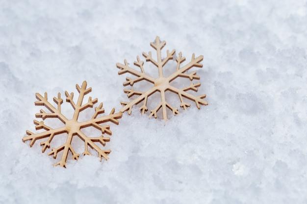 Fondo de navidad con dos copos de nieve de madera sobre la nieve. decoración navideña. fondo de vacaciones de invierno.
