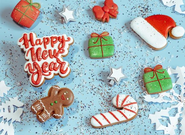 Fondo de navidad festiva con copos de nieve de papel, pan de jengibre glaseado, elementos de decoración vista superior. concepto de navidad.