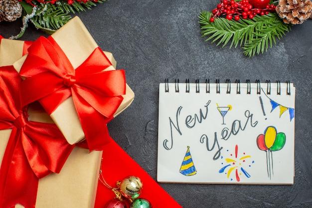 Fondo de navidad con hermosos regalos con cinta en forma de arco y accesorios de decoración de ramas de abeto cuaderno sobre una mesa oscura