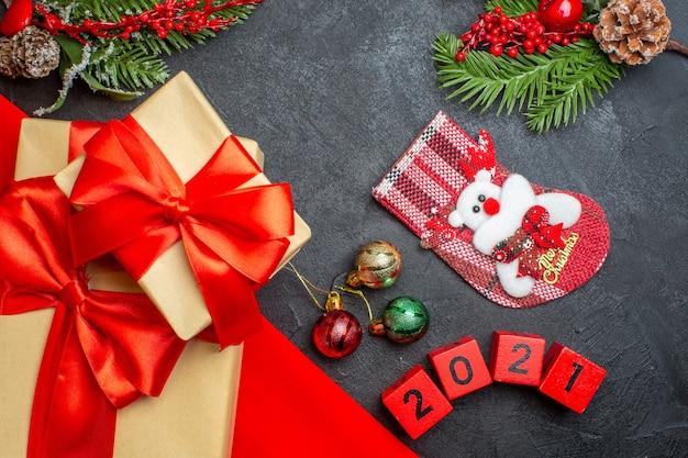 Fondo de navidad con hermosos regalos con cinta en forma de arco sobre una toalla roja y accesorios de decoración de calcetines de navidad de números en una mesa oscura
