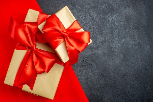 Fondo de navidad con hermosos regalos con cinta en forma de lazo sobre una toalla roja sobre un fondo oscuro